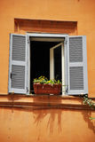 Old Romantic Window with Flower Pot. Photo of an old wooden window with a small flower pot Stock Image