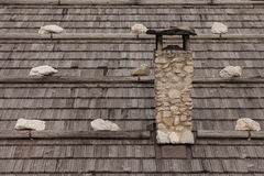 Old roof built up with wooden panels and stones. A small chimney in foreground Royalty Free Stock Photography