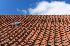 An old roof with burnt tiles. Roof in village house against a blue sky background stock image