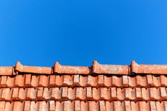 An old roof with burnt tiles. Roof in village house against a blue sky background. Stock Photography