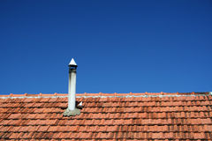 Old roof with chimney. In front of blue sky Stock Image