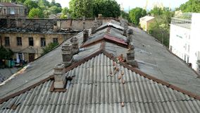 Old roof with chimneys, as well as a roof destroyed by fires in an old house in the city of Odessa in Ukraine. Bad living conditions. Housing poor people stock footage
