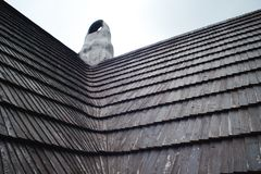 Old roof made of wooden shingles. Traditional architecture in Europe stock photos