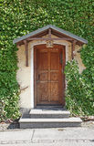 Old roofed door and overgrown house front Royalty Free Stock Image