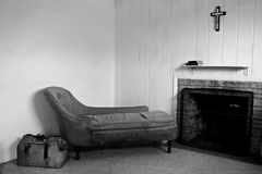 Old room. Run down room with old sofa and travel bag. There is also a fireplace and a crucifix hanging above the shelf which has two books on it Stock Images