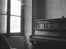 Old room with a piano in black and white. An old piano in a dark and dirty room with spider's web Royalty Free Stock Photos