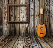 Old room. Ukulele and picture frame in vintage wood room Stock Photos