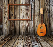 Old room. Ukulele and picture frame in vintage wood room Stock Photography