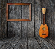 Old room. Ukulele and picture frame in vintage wood room Stock Photo