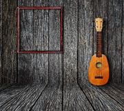Old room. Ukulele and picture frame in vintage wood room Royalty Free Stock Photography
