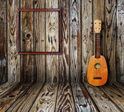 Old room. Ukulele and picture frame in vintage wood room Royalty Free Stock Images