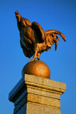 Old Rooster Bronze Sculpture over Deep Blue Sky Stock Photos