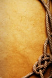 Old rope and knot on paper. An old rope tied in a knot on aged brown paper. Room for text available Royalty Free Stock Photo