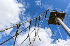 Old rope ladder and mast against cloudy sky Stock Photo