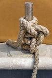 Old rope tied around stainless steel pillar. Close up view of old natural rope tied around stainless steel pillar on a fisherman boat Royalty Free Stock Photos