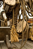 Old rope and wooden block pulleys. An old rope and wooden block pulleys of an old pirate ship royalty free stock photo