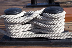 Old ropes around mooring bollard Royalty Free Stock Images