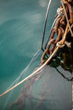 Old ropes and rusty mooring chains at sea water Stock Image