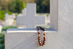 Old rosary on cemetery cross Royalty Free Stock Image