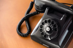 Old rotary dial phone. Old fashioned retro rotary dial phone on wooden desk, closeup Stock Image