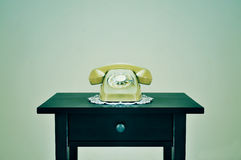 Old rotary dial telephone on a table, with a retro effect Royalty Free Stock Photo