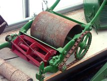 Old rotary lawnmower. An old retired rotary lawnmower kept on a shelf mothballed. Other machines beside it. Coloured red and green. Rusty equipment Royalty Free Stock Image