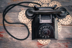 Old rotary phone on a decorative criocheted doily Royalty Free Stock Image