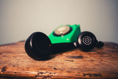 Old rotary phone on a wooden desk. Old retro rotary phone on a wooden desk Stock Image