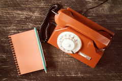Old rotary telephone and spiral notebook Royalty Free Stock Images