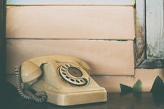 Old rotary telephone on wooden table with vintage filter background Royalty Free Stock Images