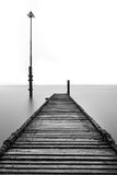 Old Rotted Jetty With Lamppost. A black and white photograph of an old abandoned jetty on the Irish Coast at Llandudno in Wales, UK. The jetty is disused and Royalty Free Stock Image
