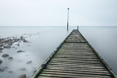 Old Rotted Jetty With Rocks And Sea Mist. Stock Images