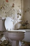 Old, rotten bathroom. With toilet, peeling paint and garbage Royalty Free Stock Image