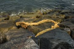 Old rotten hemp rope on the rocky shore. The sea waves lap at the shore and ebb. All the big dark rocks are hit by the waves Stock Photography