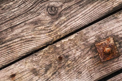 Old Rotten Planks With Rusty Nails And Square Washer With Screw Nut. Old, weathered, rotten planks, with lateral cracks and in-between splits, embedded rusty Stock Images