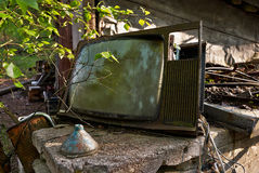 Old rotting 70's television. Rotting electronics become part of nature at a junkyard. Finnish old tube television from the 70's Royalty Free Stock Photography