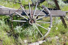 Old rotting wagon wheel. Old abandoned wagon wheel rotting away. You can see part of the wagon Royalty Free Stock Photo