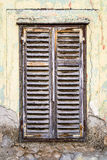 Old rotting wooden window. On the crumbling wall Stock Images