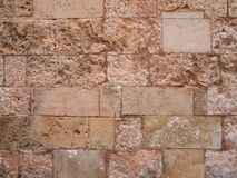 Old rough brown stone wall built of large worn blocks with damaged stones repaired. An old rough brown stone wall built of large worn blocks with damaged stones royalty free stock images