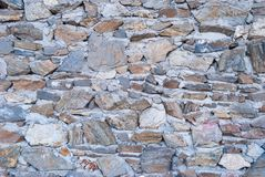 Old rough granite stone wall texture background closeup.  stock photos