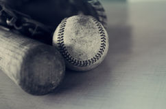 Old rough and rugged baseball and vintage wooden bat on blue texture background. Old wooden bat showing grains laying beside vintage ball and leather mitt.  All Stock Photos