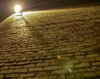 Old rough and uneven brick wall illuminated by a lantern, bottom view royalty free stock image