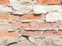 Old rough wall with red bricks. Uneven surface of old wall with old chipped bricks, held together by a rough gray cement royalty free stock photo