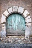 Old round door and paved steet in a village Royalty Free Stock Image