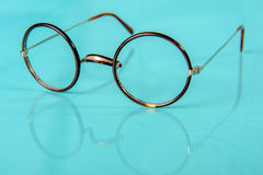 Old round glasses on reflective ground Stock Photography