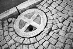 Old round hatch in urban stone pavement Stock Photography
