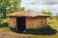 Old round house with thatched roof. Rural landscape Stock Photos