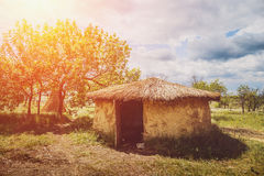 Old round house with thatched roof in sunlight. Rural landscape Royalty Free Stock Images