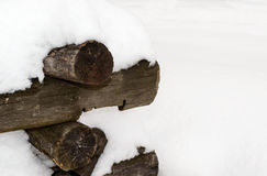 The old round logs stacked heap covered with snow. Royalty Free Stock Photography
