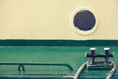 Old round porthole and black mooring bollard Royalty Free Stock Images